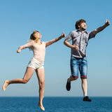 Carefree couple jumping by sea ocean water. Royalty Free Stock Photography