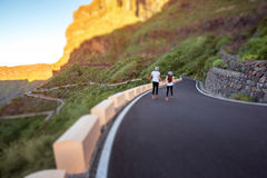 Carefree couple running on the mountain roadside Royalty Free Stock Image