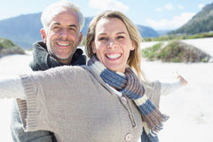 Carefree couple standing on the beach in warm clothing Stock Images