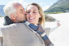 Carefree couple standing on the beach in warm clothing Royalty Free Stock Photo