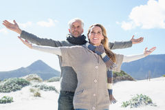 Carefree couple standing on the beach in warm clothing. On a bright but cool day Royalty Free Stock Images