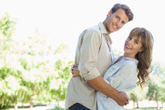 Carefree couple standing in the park and hugging smiling at camera Stock Photos