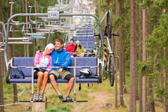 Carefree couple traveling by chair lift wood Stock Photography