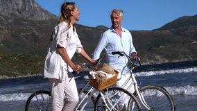 Carefree couple walking on the beach with their bikes stock video