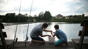 Carefree dad and son preparing to fish on the lake stock footage