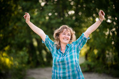 Carefree dancing mature woman against nature background Stock Photo