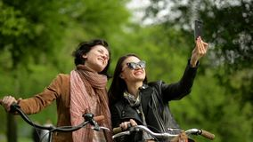 Carefree Dark-haired Women are Taking Photo of Themselves Using Smartphone Outdoors. Two Pretty Girls with Bicycles. Making Selfie by Phone in the Park, HD stock video footage