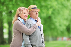 Carefree elderly couple hugging in park Stock Photos