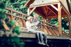 Carefree elderly couple reading a book on the wooden bridge royalty free stock photography