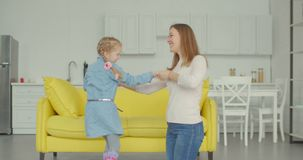 Joyful little girl with mother dancing together. Carefree excited cute elementary age daughter with pigtails and smiling attractive mother holding hands and