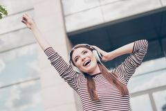 Carefree excited girl is listening to favourite song outside, wa. Lking on the spring street, wearing cozy outfit, modern headphones, dancing and singing Royalty Free Stock Images
