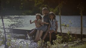 Carefree family dangling legs into water at sunset. Carefree multi ethnic family with two adorable elementary age daughters sitting on wooden pier, dangling stock video footage