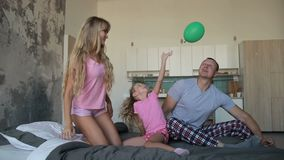 Carefree family in pajamas playing together on bed stock footage