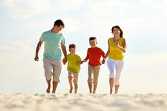 Carefree family. Photo of happy family running down the beach on summer royalty free stock photos