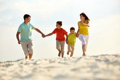 Carefree family. Photo of happy family running down the beach on summer royalty free stock photography