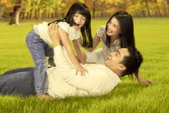 Carefree family playing at autumn park. Portrait of happy asian family enjoying holiday by playing together on the autumn park royalty free stock photo