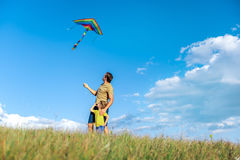 Carefree family playing with flying toy on meadow. Happy father and son are launching colorful kite on grassland together. They are looking up to the sky with royalty free stock photography
