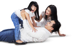 Carefree family playing in the sudio. Joyful asian family laughing and playing together on the floor, shot in the studio isolated on white Royalty Free Stock Photography