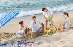 Carefree family of six people playing together on beach. Large carefree family of six people playing together with sand and active games on beach on summer day stock photography