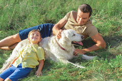 Carefree family spending time together on meadow. Enjoying summertime together. Happy boy is lying on grass and leaning on his dog back with relaxation. His Royalty Free Stock Photography