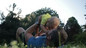 Carefree father holding cute baby son up outdoors stock footage