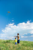 Carefree father and son launching kite on meadow. Back view of cheerful parent and kid watching the kite is flying on the sky with interest. They are standing on Royalty Free Stock Photos