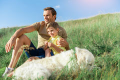 Carefree father and son spending time together on meadow. Dreamful parent and child relaxing in nature together. Man is embracing the boy and looking forward Stock Photo