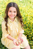 Carefree female child enjoying nature on meadow. Portrait of cute little girl sitting on grassland and holding butterfly in her hands. She is looking at camera Stock Photography