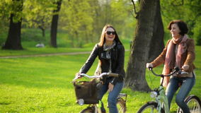 Carefree Female Friends are Riding Together and Smiling. Two Pretty Women with Bicycles are Having Fun Outside in the stock video footage