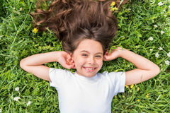 Carefree female kid relaxing on meadow. Portrait of happy little girl lying on grass with relaxation and smiling. Top view Stock Photo