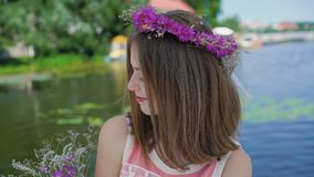 Carefree female teen with bouquet of flowers looks around on windy bay bar 4K. Pretty carefree female teen with bouquet of flowers looks around on windy bay bar stock video footage