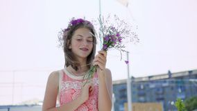 Carefree female teen with bouquet of flowers looks around on windy bay bar 4K. Pretty carefree female teen with bouquet of flowers looks around on windy bay bar stock footage