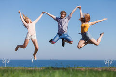Carefree friends jumping by sea ocean. Stock Photos
