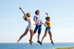 Carefree friends jumping by sea ocean. Stock Photo