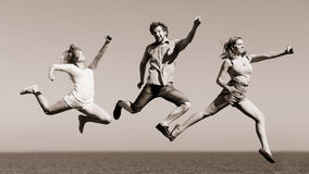 Carefree friends jumping by sea ocean water. Royalty Free Stock Images