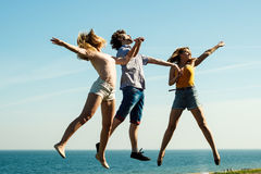 Carefree friends jumping by sea ocean water. Royalty Free Stock Image