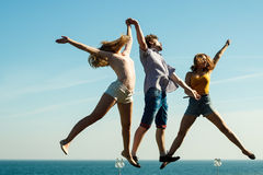 Carefree friends jumping by sea ocean water. Stock Images