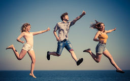 Carefree friends jumping by sea ocean water. Royalty Free Stock Photography
