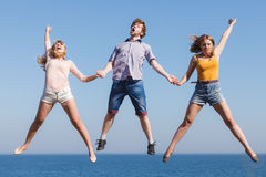 Carefree friends jumping by sea ocean water. Stock Photos