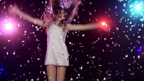 Carefree girl dancing and throws glitter confetti against disco lights. Carefree girl with long hair in short dress dancing and throws glitter confetti on black stock video footage