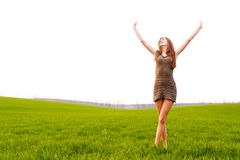 Carefree girl in green field. Happy young red haired girl with outstretched arms in green field with white sky background and copy space Stock Images
