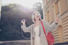 Carefree girl is listening to favourite song and dancing outside. Wearing cozy outfit and sunglasses, red backpack Royalty Free Stock Photo