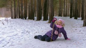 Carefree girl lying on snow in winter forest. Funny girl play in winter forest stock video