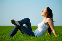Carefree girl sitting at the field Royalty Free Stock Image