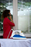 Carefree girl talking on the phone forgetting about the iron on the ironing board Stock Image
