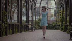 Carefree girl talking on phone while walking outdoors stock video footage