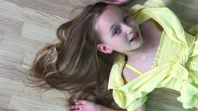 Carefree girl teenager lying down on wooden floor smiling to camera. Happy girl model posing front camera on wooden. Floor background. Right above top view stock video