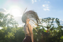 Carefree girl with zizi cornrows dreadlocks dancing on green lawn Royalty Free Stock Photography
