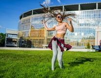 Carefree girl with zizi cornrows dreadlocks dancing on green lawn Stock Image