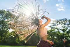 Carefree girl with zizi cornrows dreadlocks dancing on green lawn Stock Photos